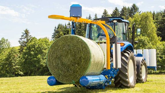 The bale is picked up using the roller arms.
