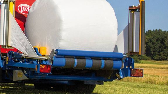 The additional roller prevents the bale from dropping off the wrapping table in steep terrain.